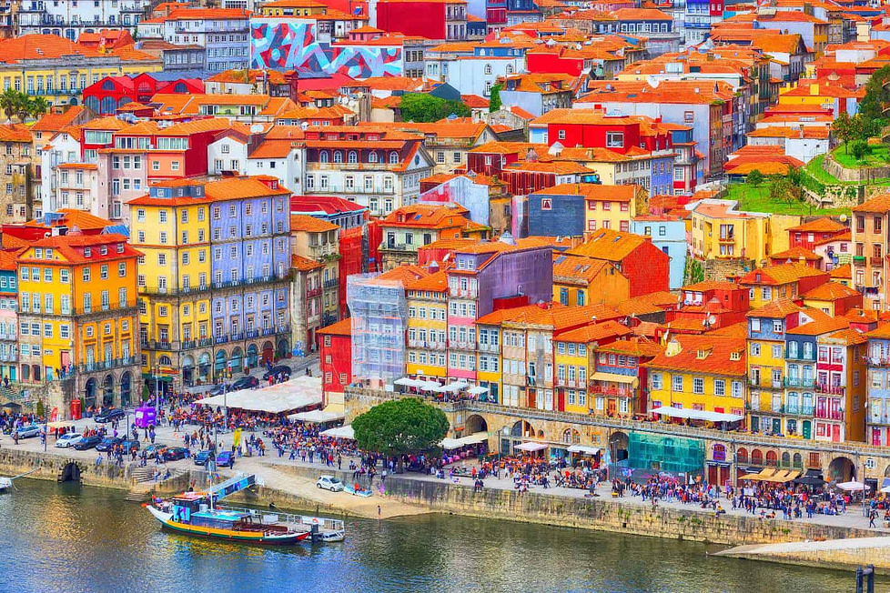Brightly coloured red and orange roofs of Porto houses along the river bank