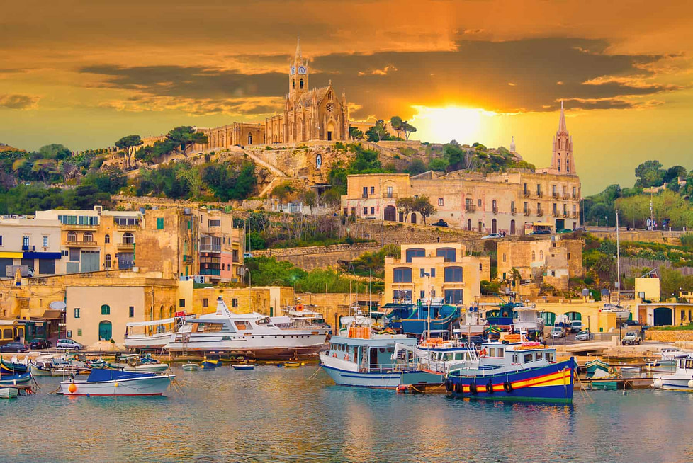 Living in Malta - Gozo island, medieval architecture of castle and boats on the harbour of Malta