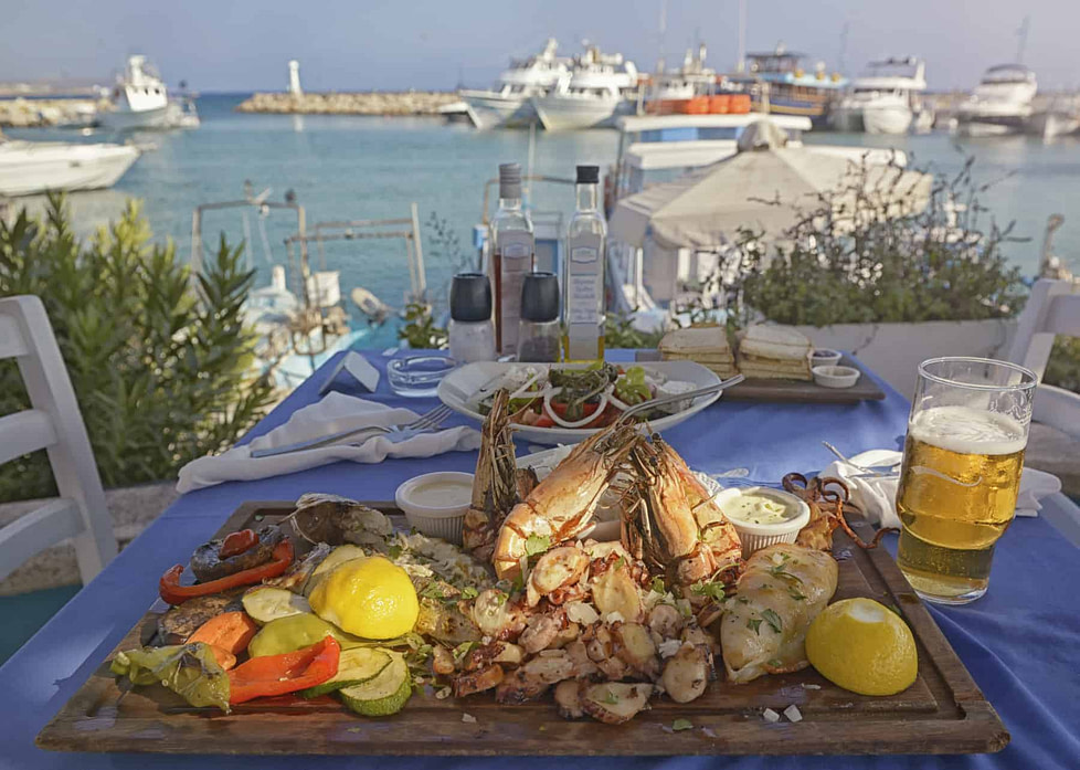A plate of seafood in an open restaurant with a seascape as a background