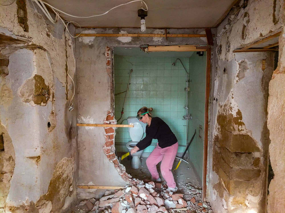 The renovation process: Emily is knocking out a wall.