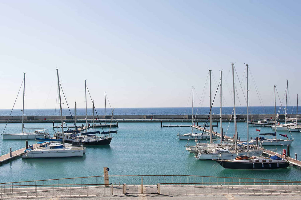 A modern marina with luxury yachts on a sunny day